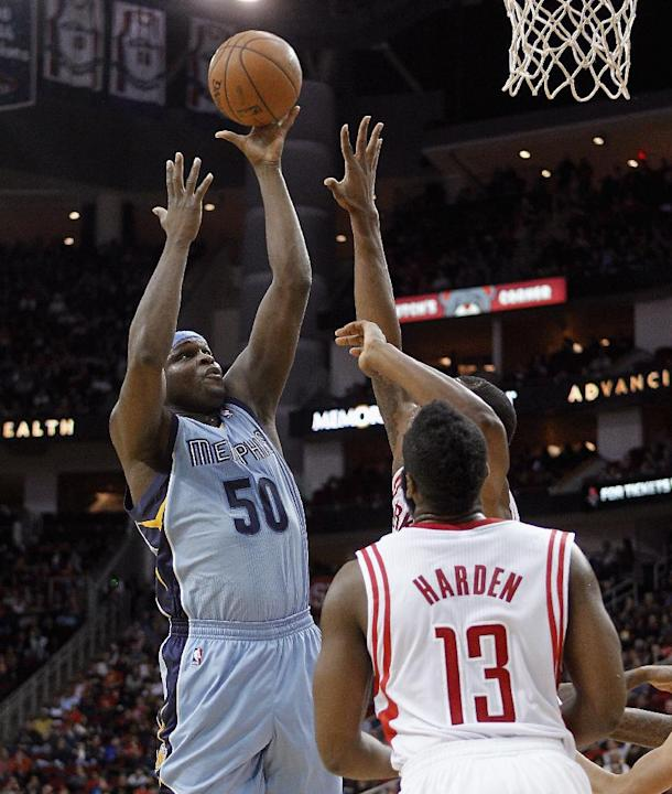 Memphis Grizzlies forward Zach Randolph, left,  drives to the basket as Houston Rockets guard James Harden (13) watches during the first half of an NBA basketball game Thursday, Dec. 26, 2013, in Hous