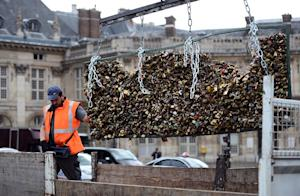 A worker removes love padlocks attached on the railings…