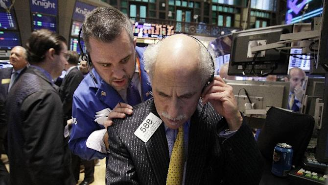 Traders Mark Lodewick, center, and Peter Tuchman, work on the floor of the New York Stock Exchange Tuesday, Oct. 11, 2011. (AP Photo/Richard Drew)