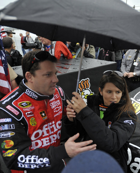 Danica Patrick, right, stands under an umbrella with Tony Stewart, left, during a rain delay in the start of the NASCAR Daytona 500 Sprint Cup series auto race in Daytona Beach, Fla., Sunday, Feb. 26,