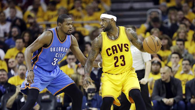 Cleveland Cavaliers' LeBron James (23) goes against Oklahoma City Thunder's Kevin Durant in an NBA basketball game Sunday, Jan. 25, 2015, in Cleveland. (AP Photo/Mark Duncan)