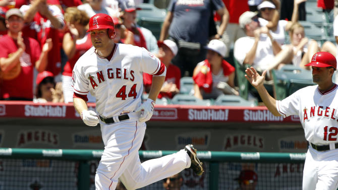 Los Angeles Angels third base coach Dino Ebel (12) congratulates Mark Trumbo (44) after Trumbo rounded third after hitting a home run against the Seattle Mariners during the third inning of a baseball game in Anaheim, Calif., Sunday, Aug. 7, 2011. The Angels won the game 2-1. (AP Photo/Alex Gallardo)