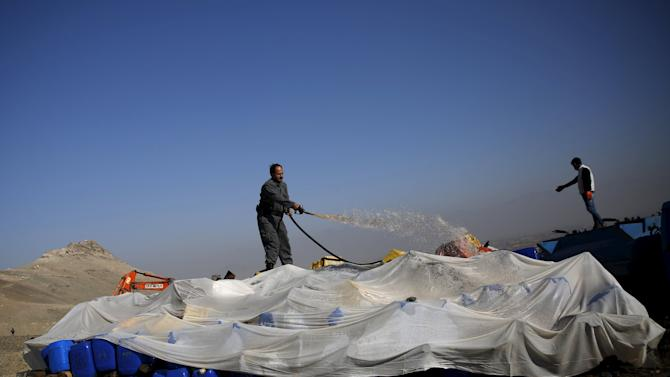 An Afghan police officer prepares to burn a pile of illegal narcotics on the outskirts of Kabul