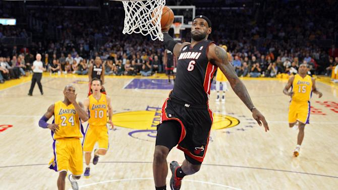 Miami Heat forward LeBron James (6) goes up for a dunk ahead of Los Angeles Lakers guard Kobe Bryant (24), guard Steve Nash (10) and forward Metta World Peace (15) during the first half of their NBA basketball game, Thursday, Jan. 17, 2013, in Los Angeles. (AP Photo/Mark J. Terrill)