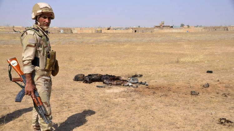 An Iraqi soldier stands near the body of a member of the Islamic State, who died during clashes with Iraqi forces, in Tikrit