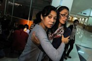 Relatives of passengers on the ill-fated Russian Sukhoi Superjet 100 wait for information at the arrival area of Halim airport in Jakarta
