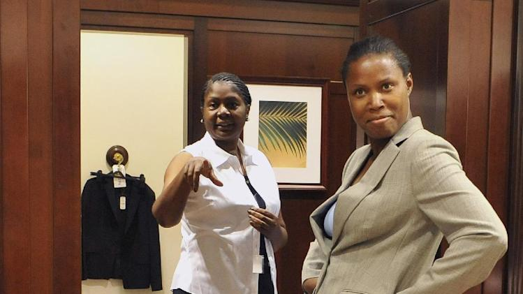In this Thursday, Sept. 20, 2012 photo, Army Reservist Tiffany Mellers of Bridgeport, Conn., right, poses for staff at a Brooks Brothers store while being fitted for a new suit as Air Force veteran Janette Blackmore of Maryland, left, looks on in West Hartford, Conn. Mellers and Blackmore are participating in the University of Connecticut's Entrepreneurship Bootcamp for Veterans with Disabilities. More than 200,000 people are discharged from the U.S. military each year, and advocates say they often possess qualities that make good entrepreneurs: resourcefulness, a taste for risk-taking and a can-do attitude. Nonprofit groups, state governments and U.S. agencies are all providing business training aimed at giving them new purpose and easing their transition to civilian life. (AP Photo/Jessica Hill)