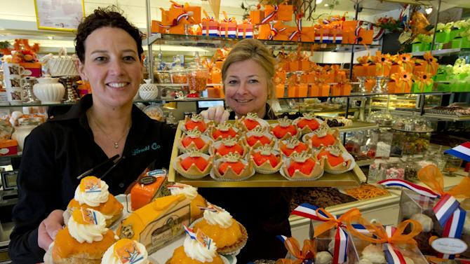 Sandra Terpstra, left, and Linda Clewits pose with trays of cakes made for Queen's Day, a national holiday and the day of the abdication of Queen Beatrix and the crowning of the new King, at a Arnold Cornelis pastry shop in Amsterdam, Netherlands, Thursday April 23, 2013. The shop was decorated with Dutch flags and the color of the Dutch royals, the House of Orange. Queen Beatrix has announced she will relinquish the crown on April 30, 2013, after 33 years of reign, leaving the monarchy to her son Crown Prince Willem Alexander. (AP Photo/Peter Dejong)