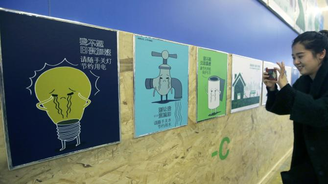 A visitor takes pictures of Chinese ecology awareness posters on display during the opening day of the World Climate Change Conference 2015 (COP21) at Le Bourget, near Paris