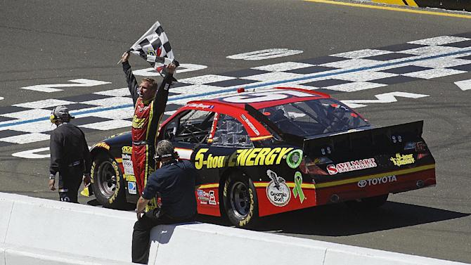 Clint Bowyer raises the checkered flag after winning the NASCAR Sprint Cup Series auto race, Sunday, June 24, 2012, in Sonoma, Calif. Bowyer ran out of gas and parked his car on the finish line. (AP Photo/Ben Margot)