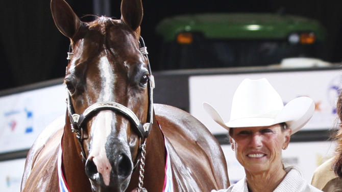 This Nov. 2011 photo provided on April 18, 2012, by The American Quarter Horse Journal, shows Rita Crundwell, of Dixon, Ill., posing with Pizzazzy Lady at the 2011 American Quarter Horse Association World Championship Show in Oklahoma City. On Tuesday, April 17, 2012, FBI agents arrested Crundwell, the Dixon comptroller, on charges that she stole more than $3.2 million in public funds from the city of Dixon in just a matter of months. She also was accused of misappropriating more than $30 million since 2006 to finance a lavish lifestyle, including operating a horse farm. (AP Photo/The American Quarter Horse Journal)