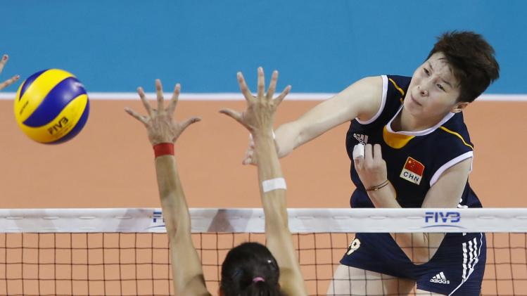 Li of China spikes the ball against Onal Pasaoglu of Turkey during their FIVB Women's Volleyball World Grand Prix 2014 final round match in Tokyo