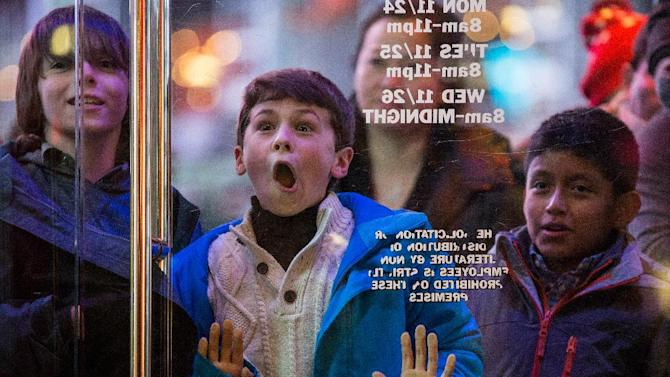 A boy waits to enter Toys'R'Us store at Times Square in New York, on November 27, 2014