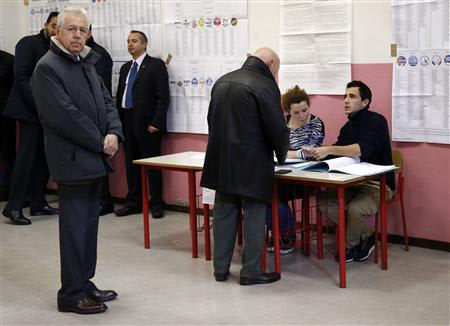 Outgoing Prime Minister Mario Monti waits before casting his vote at the polling station in Milan, February 24, 2013. Italians began voting on Sunday in one of the most closely watched elections in years, with markets nervous about whether it can produce a strong government to pull Italy out of recession and help resolve the euro zone debt crisis. REUTERS/Stefano Rellandini