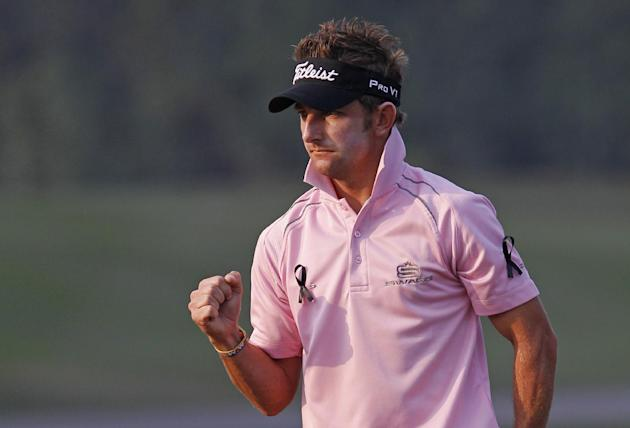 Jbe Kruger of South Africa, wearing black ribbons as a sign of his respect to the former South African President Nelson Mandela, celebrates after hitting a putt for birdie on the 17th hole during the