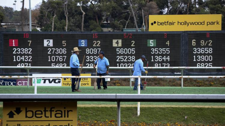 Workers tend to the turf course at Betfair Hollywood Park, which is closing down after tomorrow's race card in Inglewood, California