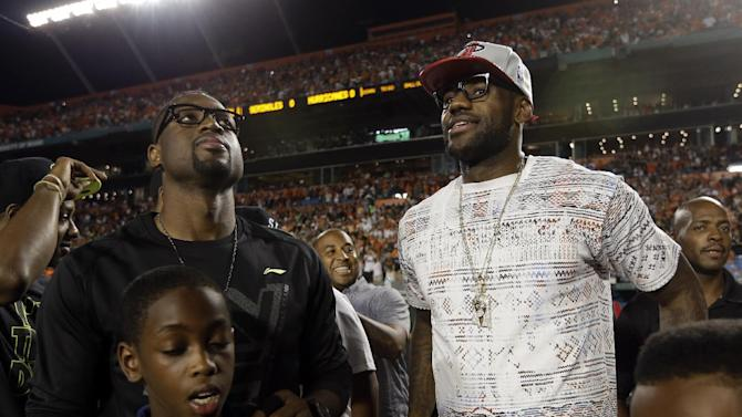 The Miami Heat's Dwayne Wade, left, and LeBron James, right, stand on the sidelines before an NCAA college football game between Miami and Florida State, Saturday, Oct. 20, 2012, in Miami. (AP Photo/Lynne Sladky)