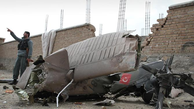 An Afghan policeman, left, gestures as he recounts a Turkish helicopter crash to others, unseen, near the wreckages of the helicopter on the outskirts of Kabul, Afghanistan, Friday, March 16, 2012. A Turkish military helicopter crashed into a house near the Afghan capital Friday, killing several Turkish soldiers on board and young girls on the ground, Turkish and Afghan officials said.  (AP Photo/Musadeq Sadeq)
