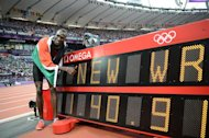 Kenya&#39;s David Lekuta Rudisha poses next to the record board after winning the men&#39;s 800 final at the athletics event during the London 2012 Olympic Games on August 9, 2012 in London. Rudisha clocked a new world record of 1min 40.91sec. AFP PHOTO / FRANCK FIFE
