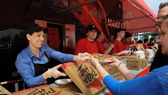 IMAGE DISTRIBUTED FOR PIZZA HUT - Pizza Hut team members including Betty Olvera, left, dish out free slices of pizza to more than 2000 Microsoft employees as part of the Pizza Hut for Xbox LIVE Ordering App Launch at the Microsoft campus on Tuesday, April 23, 2013 in Redmond, WA. (Rod Mar/AP Images for Pizza Hut)