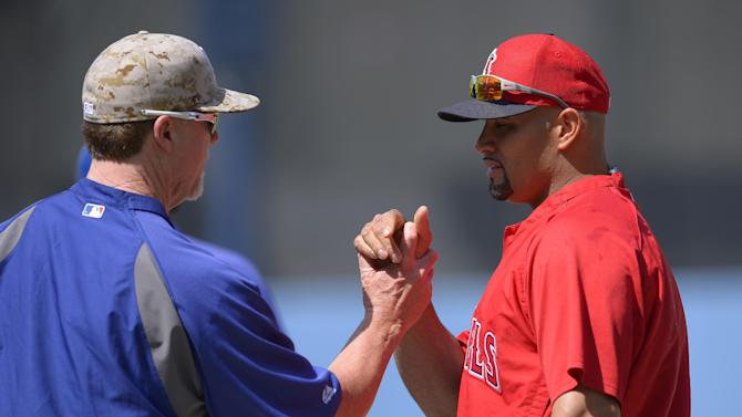 Los Angeles Dodgers batting coach Mark McGwire, left, greets Los Angeles Angels first baseman Albert Pujols during batting practice prior to their baseball game, Monday, May 27, 2013, in Los Angeles. (AP Photo/Mark J. Terrill)