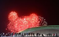 People watch the fireworks exploding over the Russian Black Sea resort of Sochi, on February 7, 2013, to celebrate the one year countdown to the Sochi 2014 Winter Olympics opening. A year before athletes converge on Sochi for the Winter Olympics, the Russian seaside city remains a vast construction site, with traffic choking the streets and locals bracing for another year of nonstop work