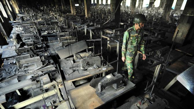 FILE - In this Sunday, Nov. 25, 2012 file photo, a Bangladeshi police officer walks past rows of burnt sewing machines in the burned out Tazreen garment factory in Savar, on the outskirts of Dhaka, Bangladesh. Government investigators said the November fire at the Tazreen factory, which killed 112, was so deadly in part because clothing was stored in the stairwell, which turned the emergency exit into a chimney billowing smoke, fire and toxic fumes from the burning fibers. (AP Photo/Khurshed Rinku, File)