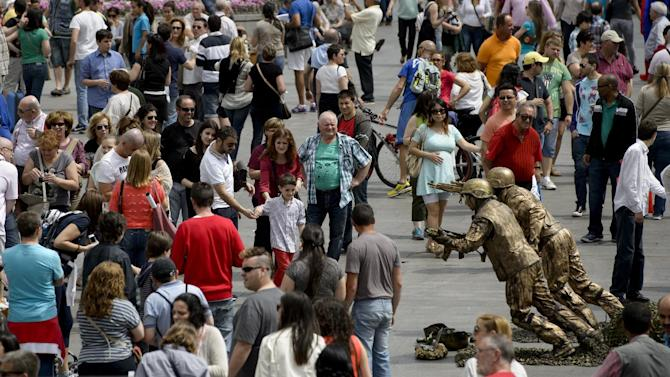 Tourists walk past men performing as living statues in the Puerta del Sol Square in Madrid on April 19, 2014