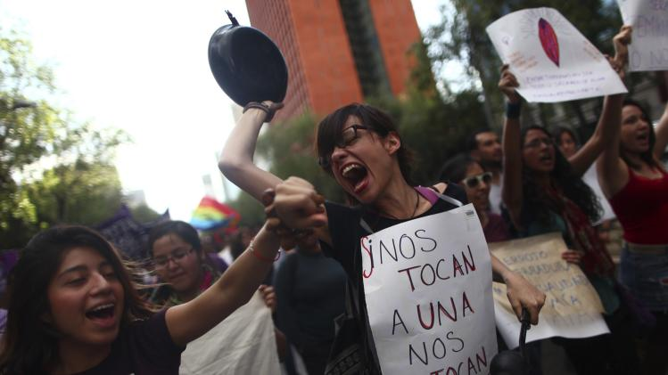 A woman yells while holding up a pan during a march to mark International Women's Day in Mexico City