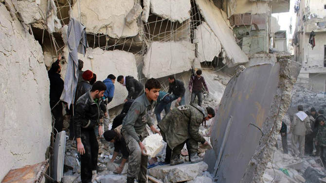 In this citizen journalism image provided by Aleppo Media Center (AMC), an anti-Bashar Assad activist group, which has been authenticated based on its contents and other AP reporting, Syrians inspect the rubble of destroyed buildings following a Syrian government airstrike in Aleppo, Syria, Friday, Jan. 31, 2014 . Activists said the latest Syrian government shelling has killed and wounded several people in a rebel-held area of the northern city of Aleppo. (AP Photo/Aleppo Media Center, AMC)
