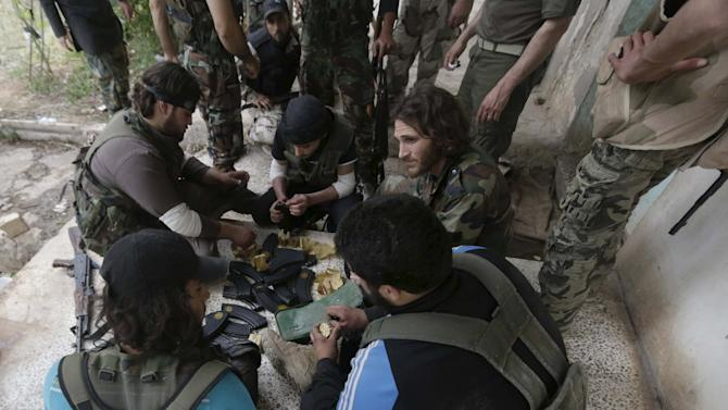 Rebel fighters prepare their ammunition in Aleppo's Sheikh Saeed neighbourhood