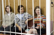 "From left, Yekaterina Samutsevich, Nadezhda Tolokonnikova, Maria Alekhina, members of feminist punk group Pussy Riot sit behind bars at a court room in Moscow, Russia, Friday, July 20, 2012. The trial of feminist punk rockers who chanted a ""punk prayer"" against President Vladimir Putin from a pulpit inside Russia's largest cathedral started in Moscow on Friday amid controversy over the prank that divided devout believers, Kremlin critics and ordinary Russians. (AP Photo/Misha Japaridze)"