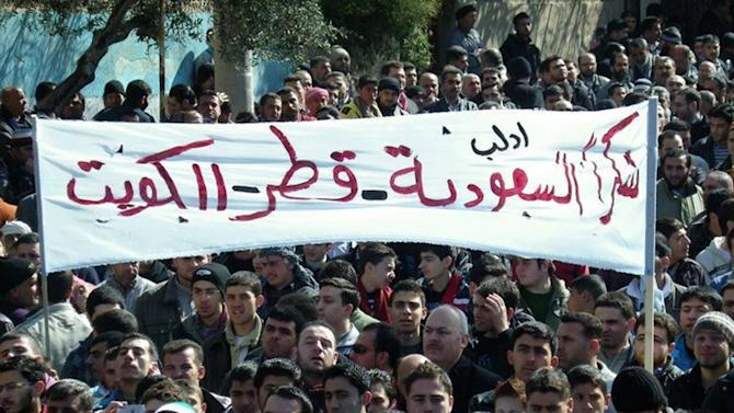 """FILE -- In this March 2, 2012 file photo, Citizen journalism image provided by Local Coordination Committees in Syria, which has been authenticated based on its contents and other AP reporting, anti-Syrian regime protesters hold up a banner in Arabic reading: """"thank you Saudi Arabia, Qatar and Kuwait,"""" during a demonstration, in Idlib province, northern Syria. Qatari support for Islamist-learning rebels is causing tensions within the ranks of the highly fragmented Syrian opposition movement. The hyper-wealthy Gulf emirate wields enormous influence over the Syrian opposition's political structure but increasingly faces a backlash among rebel fighters who are wary about potential bargains that could end up giving Qatar outsized influence over the country in a post-Assad transition. (AP Photo/Local Coordination Committees in Syria, File)"""