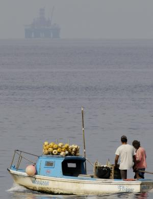 An oil rig floats in the distance as fishermen work in Havana Bay, Cuba, Thursday Jan. 19, 2012. The Chinese-built oil rig arrived to Cuba to start exploratory drilling beneath the waters off Cuba's northern coast. Cuban leaders hope the rig will bring riches to a Communist country that is sorely in need of an economic boost. Spanish company Repsol is carrying out the exploratory effort under a contract with the Cuban government. (AP Photo/Javier Galeano)