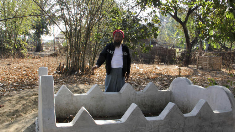In this Feb. 27, 2014 photo, Mohamad Frukan stands next to the grave of his wife Noor Jahan, an ethnic Rohingya who died due to kidney disease, in The' Chaung village, north of Sittwe, Rakhine state, Myanmar. (AP Photo/Pyae Phyo Thant Zin)