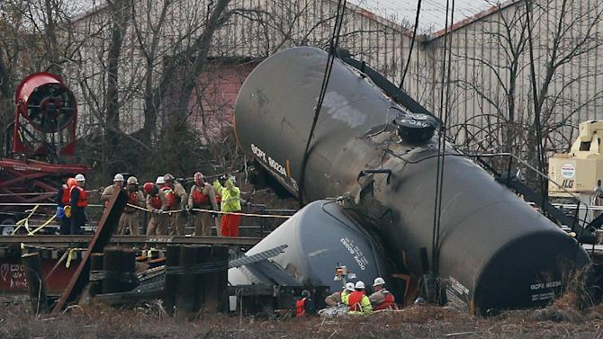 Workers secure lines around a train tank car as they prepare to pull it up with a crane from a crash site on a small bridge on the Mantua Creek, Tuesday, Dec. 11, 2012, in Paulsboro, N.J. The tank car was the first to be removed as officials continued to clean up after the accident. Hazardous gas spewed from a ruptured freight train car during the accident, which occurred Nov. 30, 2012. Precautionary evacuations were ordered late after readings showed higher levels of vinyl chloride in the air. (AP Photo/Julio Cortez)