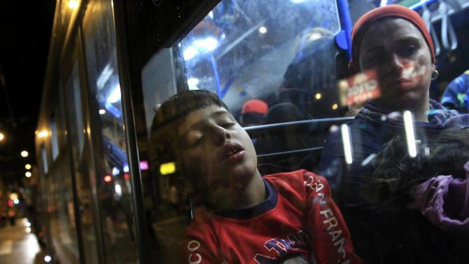 A boy sits in a bus, which is supposed to leave to Austria and Germany, at the Keleti trainstation in Budapest