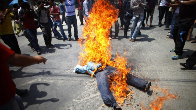 Activists of Nepali Congress-affiliated Nepal Students Union burn an effigy of Prime Minister Baburam Bhattarai as they demand his resignation in Katmandu, Nepal, Monday, May 28, 2012. Nepal sank into political turmoil Monday after lawmakers failed to agree on a new constitution, leaving the country with no legal government. (AP Photo/Niranjan Shrestha)