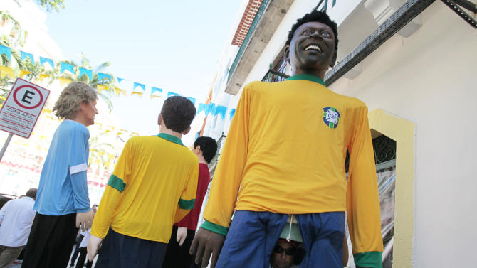 A man looks out of a giant Pele effigy as he waits with the effigies of Uruguayan striker Diego Forlan, Brazil's Neymar and Spain's Andres Iniesta for their performance at a promotional event of the soccer Confederations Cup in Recife, Brazil, Tuesday, June 18, 2013. (AP Photo/Eugene Hoshiko)