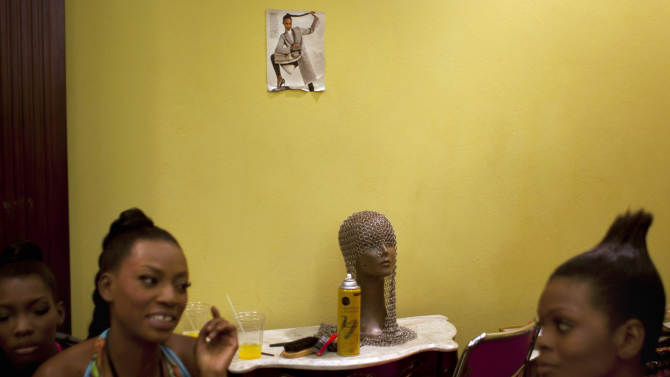 Models chat backstage while waiting to hit the catwalk at Haiti Fashion Week in Port-au-Prince, Haiti, Friday, Nov. 9, 2012. (AP Photo/Dieu Nalio Chery))
