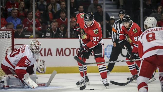 Chicago Blackhawks' Brad Richardson tries to control the puck in front of Detroit Red Wings goalie Jonas Gustavsson in an NHL exhibition hockey game in Chicago on Tuesday, Sept. 23, 2014. (AP Photo/Charles Cherney)