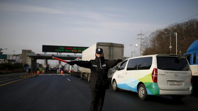 A security guard directs traffic as South Korean vehicles transporting employees working at North Korea's Kaesong Industrial Complex (KIC) pass a gateway at the South's CIQ, in Paju