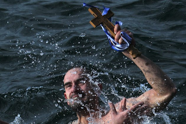 Giorgos Ypsilantis, holds up the wooden cross after being the first to retrieve it, during an Epiphany ceremony to bless the water in Greece's northern port city of Thessaloniki, on Sunday, Jan. 6, 20
