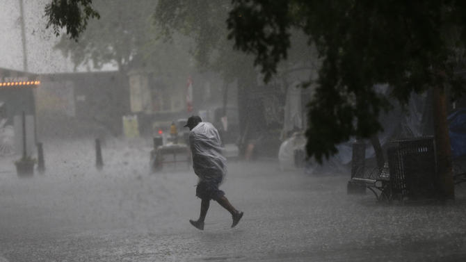 A person runs for shelter in Jackson Square during a heavy downpour on the first day of the annual French Quarter Festival in New Orleans, Thursday, April 11, 2013.  French Quarter Festival, which turns 30 this year, runs through Sunday and showcases Louisiana food and music on stages strung throughout the historic neighborhood, including Jackson Square, the French Market, along narrow streets and on the Mississippi riverfront. The lineup includes Irma Thomas, trumpeter Kermit Ruffins, Cajun fiddler Amanda Shaw, the Dirty Dozen Brass Band and about 250 other acts. (AP Photo/Gerald Herbert)