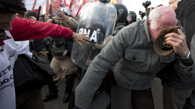 A demonstrator covers his face from pepper sprayed by police trying to keep the road partially open to traffic in Buenos Aires, Argentina, Thursday, Aug. 28, 2014. Truck drivers, restaurant workers and some members of education unions joined a 24-hour walkout on Thursday, as a more radical opposition labor union continued their 36-hour strike that started Wednesday. The protests over taxes, wages and the overall cost of living in the country, come amid deepening economic troubles for Argentina, with the economy in recession and inflation running around 40 percent. (AP Photo/Natacha Pisarenko)