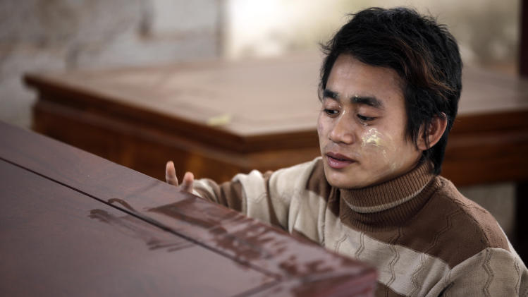 In this May 25, 2012 photo, a Burmese worker finishes a table at a rosewood furniture factory in Ruili, near Myanmar border, Yunnan Province, China. This remote southwestern Chinese city of about 140,000 nestled in a river valley on the Myanmar border amassed huge wealth over decades of trade and smuggling of drugs, timber and jade. Now, China's main trading gateway to its long-isolated neighbor is waiting for a new boom that may never come. (AP Photo/Eugene Hoshiko)