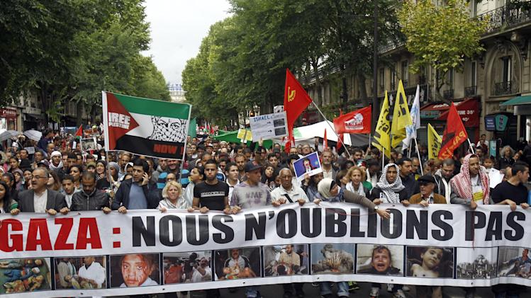 "Thousands of pro-Palestinian demonstrators holding banners and chanting anti Israeli slogans walk in Paris, Sunday July 13, 2014, to protest against the Israeli army's bombings in the Gaza strip. Banner reads: ""Gaza, We Will Not Forget"". About 10,000 pro-Palestinian protesters marched through eastern Paris on Sunday demanding an end to Israeli strikes on Gaza, and accusing Western leaders of not doing enough to stop them. (AP Photo/Remy de la Mauviniere)"