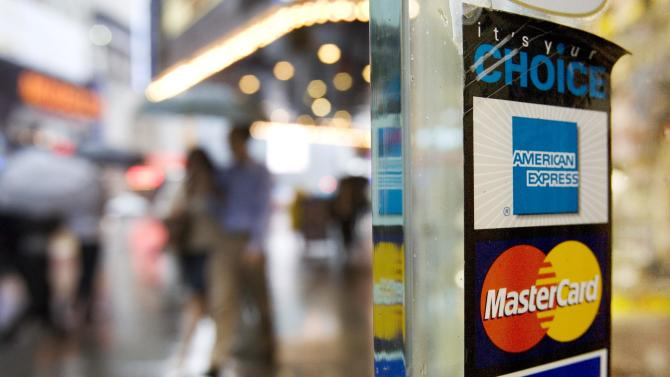 FILE - In this July 27, 2007, file photo, signs for American Express, Master Card and Visa credit cards are shown on a New York store's door. American Express says its net income fell 47 percent in the fourth quarter of 2013, as the credit card issuer racked up hefty charges related to restructuring costs and other one-time expenses. (AP Photo/Mark Lennihan, File)