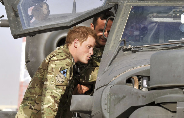 FILE - Photo dated 7/9/2012 of Britain's Prince Harry examining the cockpit of an Apache helicopter with a member of his squadron (name not provided) at Camp Bastion in Afghanistan, where he will be operating from during his tour of duty as a co-pilot gunner. The prince was unharmed after an attack on the Camp Bastion compound in which two US Marines were killed and several more wounded Saturday Sept. 15, 2012. US officials said the attack last night was by heavily-armed insurgents and involved a range of weaponry, including mortars, rockets or rocket-propelled grenades, as well as small arms fire. Harry was about two kilometres away with other crew members of the Apache attack helicopters, when the attack took place, sources said. (AP Photo/John Stillwell/pool file)