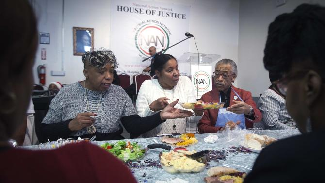 Civil rights activist Reverend Al Sharpton and Eric Garner's mother Gwen Carr and widow Esaw Garner eat Christmas dinner in the Harlem section of New York